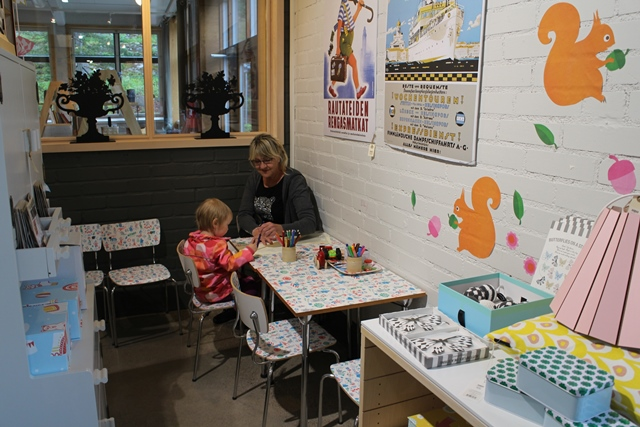 Perheen pienimmille löytyy oma piirustuspaikka. Anni oli tullut tutustumaan näyttelyyn Porvoosta äitinsä ja Ritva-mummmin (kuvassa) kanssa. Kuva: KivaaTekemistä.fi