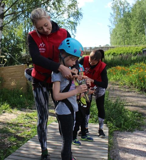 Ninja ja Anna kiinnittävät lapsille turvavaljaita. Kuva: KivaaTekemistä.fi