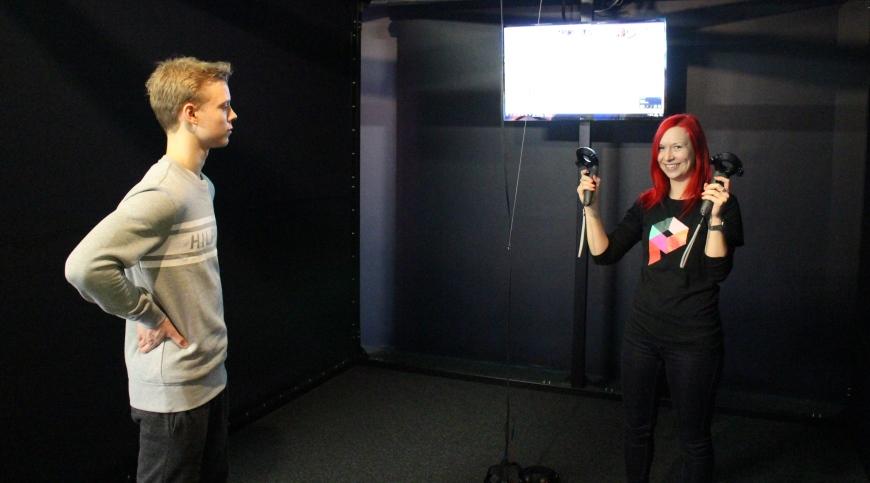 Elina opastaa peliohjainten käyttöä Danielille. Kuva: KivaaTekemistä.fi