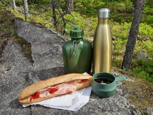 Aamiaistarjoilu Sipoonkorvessa. Täytetty patonki, vesipullo, kahvitermos ja kahvimuki.